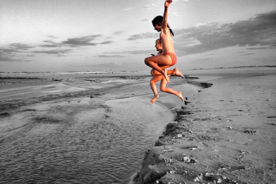 girls jump at beach